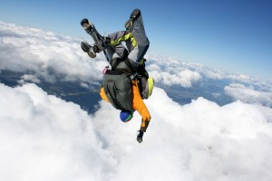 Two skydivers in free fall on a sunny day in cloudy sky head down